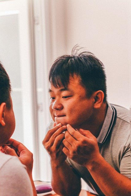man inspecting acne in a mirror