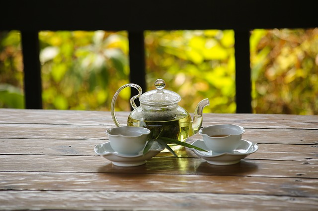 Bamboo Tea in a glass tea pot with two cups on saucers on a wooden table