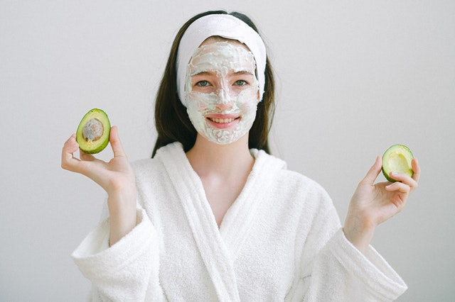 Lady wearing an avocado face mask in a white robe holding a halved avocado