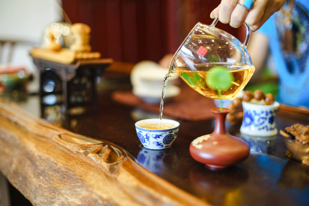 A hand pouring Lapsang Souchong Tea into a cup from a glass teapot.