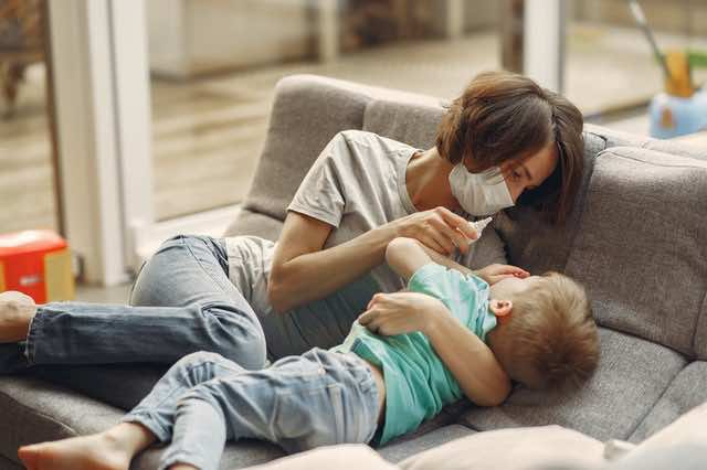 Mother and son on a sofa with a nasal spray in the mother's hand.