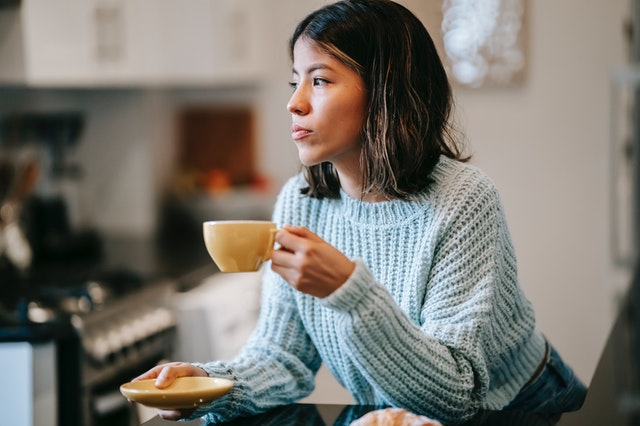 Lady drinking tea holding a saucer